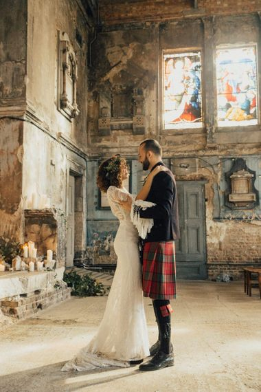 Boho Bride in Lace Rue De Seine Wedding Dress and Groom in Highland Wear Standing in The Asylum, London
