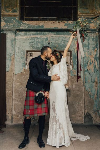 Boho Bride in Lace Rue De Seine Wedding Dress and Groom in Highland Wear Kissing in The Asylum, London
