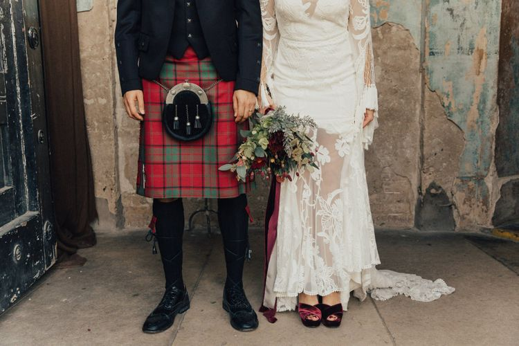 Bride and Groom in Lace Rue De Seine Wedding Dress  and Red Tartan Highland Wear