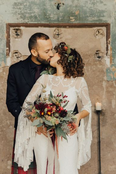 Bride in Lace Rue De Seine Wedding Dress  with Tassel Bell Sleeves and Groom in Highland Wear Kissing