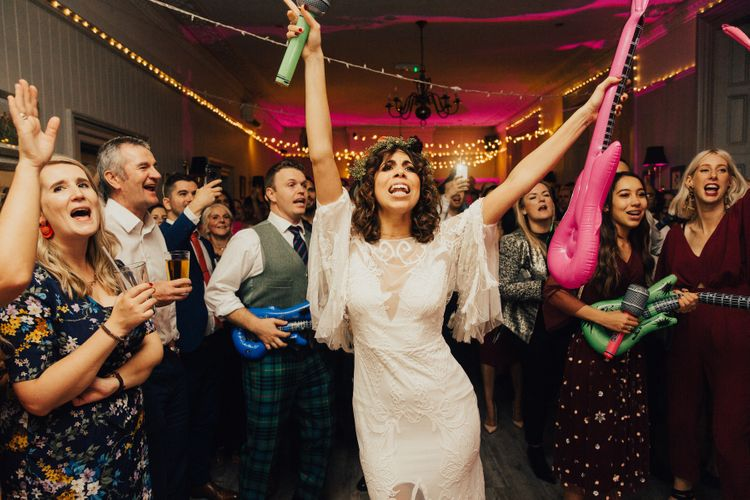 Boho Bride with Curly Hair & Flower Crown Waving Inflatable Guitars on the Dance Floor