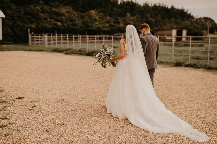 bride and groom walking through the grounds of their rustic wedding venue