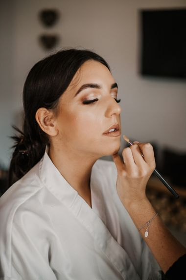 bride having her makeup done on the wedding morning