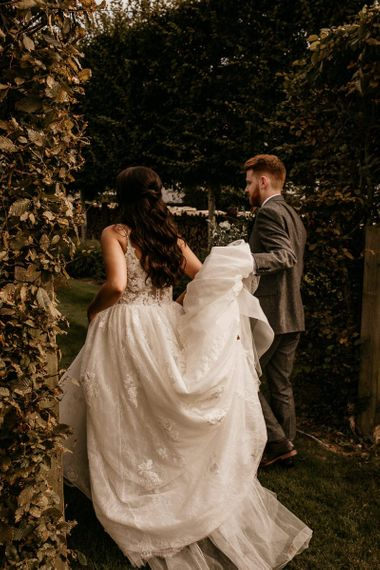 Groom helping his bride with her wedding dress train