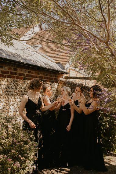 Bridesmaids in black dresses raising a toast