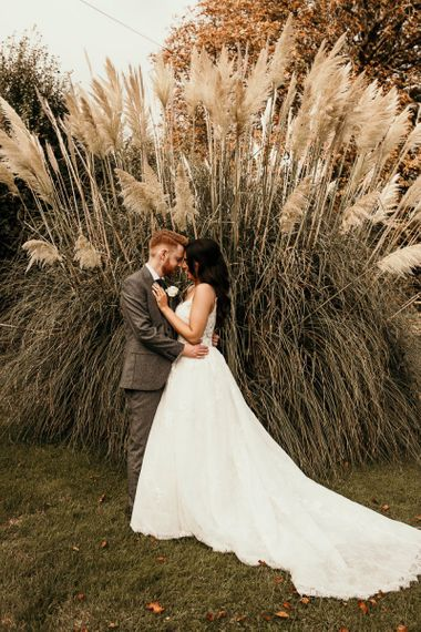 Bride and groom wedding portrait next to pampas grass plant