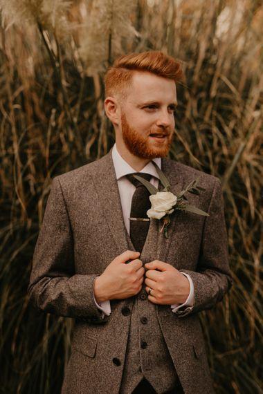 Groom in world suit for rustic wedding