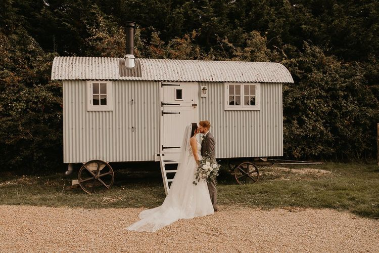 Bride and groom portrait in front of rural trailer