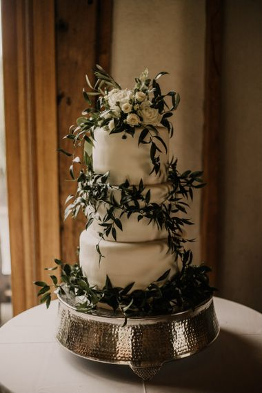 Homemade wedding cake covered in foliage