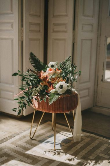 Romantic Bouquet with Anemones and Fern Tied with Ribbon Sitting on a Velvet Stool