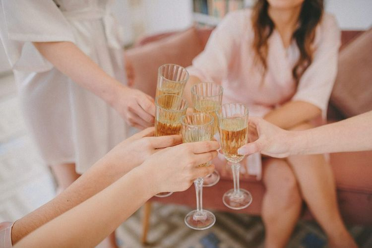 Wedding Morning Bridal Preparations with Bridesmaids Clinking Champagne Glasses