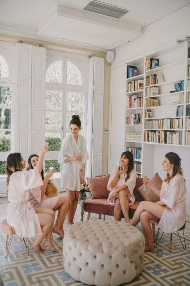 Bridal party drinking champagne in getting ready robes