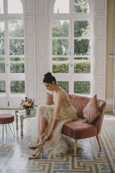 Bride in Lace Wedding Dress Putting on Bridal Shoes