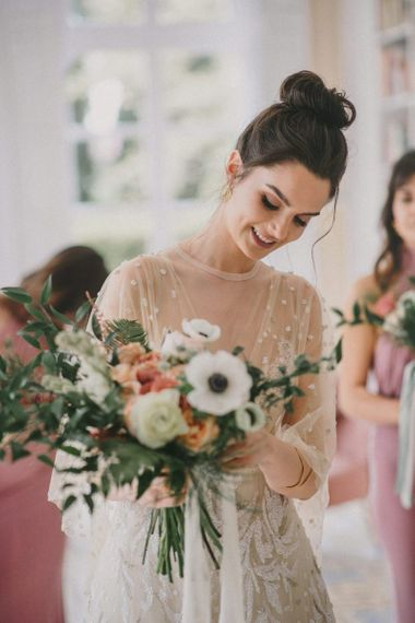 Bride with Messy Bun Looking at Her Wedding Bouquet