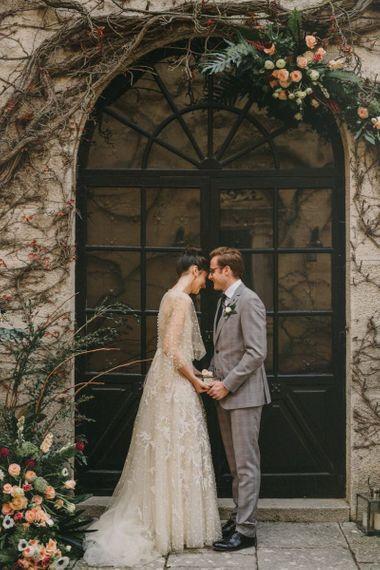 Bride and Groom Holding Hands in a Door way at Small Wedding