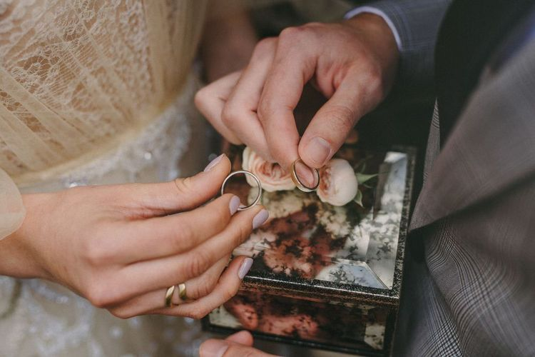 Wedding Rings in Glass Ring Box Filled with Flowers