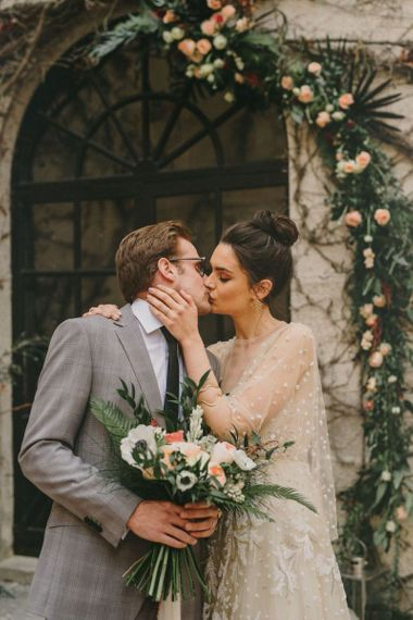 Bride with Top Knot Kissing Her Groom in a Grey Check Suit