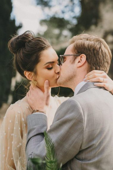 Bride with Top Knot and Gold Leaf Earrings Kissing Her Groom