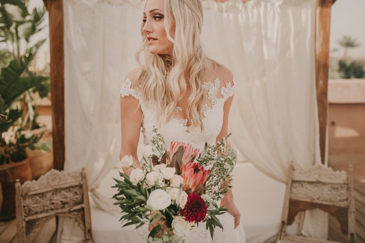 Bride in  Olvia Lace Gown from TeoKath & Oversized Bouquet | Marrakesh Wedding at Ksar Char Bagh Hotel, Planned by Instants Magiques | Pablo Laguia Photography | Monika Frias Videography