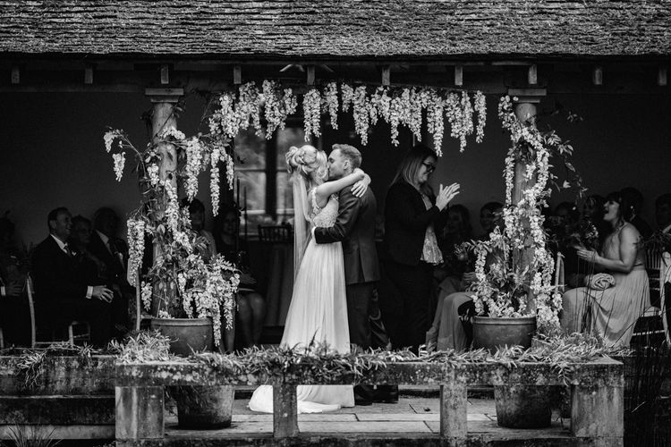 Black and White Portrait of Outdoor Wedding Ceremony with Bride in Stacey by Modeca Wedding Dress and Groom in  Charles Tyrwhitt Suit