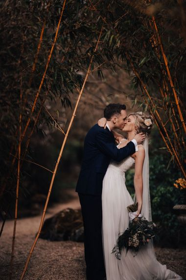 Bride in Stacey by Modeca Wedding Dress and Groom  in Charles Tyrwhitt Suit Kissing