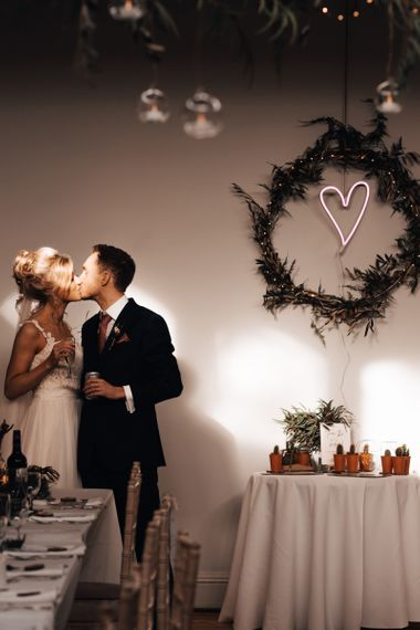 Bride and Groom Kissing with Neon Heart in Greenery Hoop