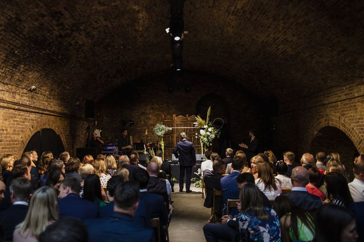 Wedding Ceremony | Groom in Navy Three Piece Suit from Yardsmen | Altar With Large Floral Features | Shoreditch Wedding at Village Underground with Bride in Grace Loves Lace | Chris Barber Photography