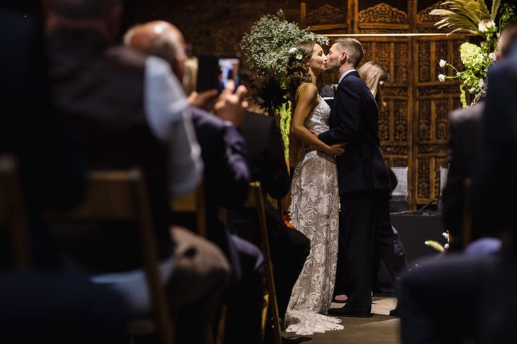 Wedding Ceremony | First Kiss | Bride in Grace Loves Lace Gown with Spaghetti Straps and Oversized Rose Embroidery | Groom in Navy Three Piece Suit from Yardsmen | Altar With Large Floral Features | Shoreditch Wedding at Village Underground with Bride in Grace Loves Lace | Chris Barber Photography