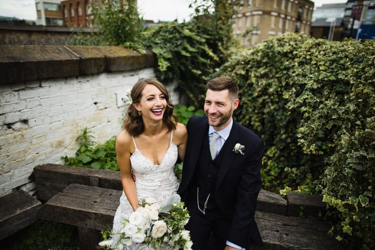 Bride in Grace Loves Lace Gown with Spaghetti Straps and Oversized Rose Embroidery | Gold Triangle Earrings | Groom in Navy Three Piece Suit from Yardsmen | Bridal Bouquet of Roses, Thistles and Foliage | Shoreditch Wedding at Village Underground with Bride in Grace Loves Lace | Chris Barber Photography