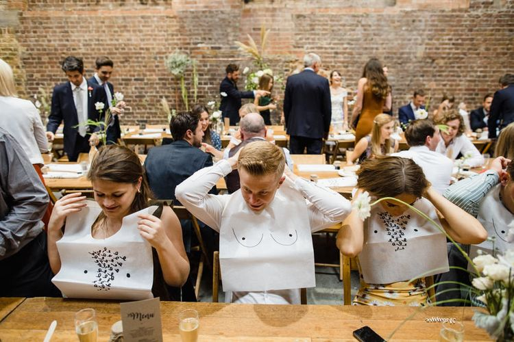 Guests Putting on Boob Bibs | Shoreditch Wedding at Village Underground with Bride in Grace Loves Lace | Chris Barber Photography