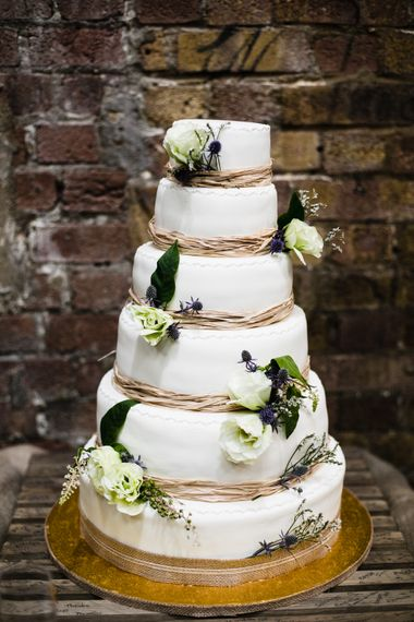 Six Tier Wedding Cake Decorated with White Roses and Thistles | Shoreditch Wedding at Village Underground with Bride in Grace Loves Lace | Chris Barber Photography