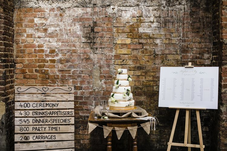 Six Tier Wedding Cake Decorated with White Roses and Thistles | Order of the Day Pallet | Seating Chart | Shoreditch Wedding at Village Underground with Bride in Grace Loves Lace | Chris Barber Photography