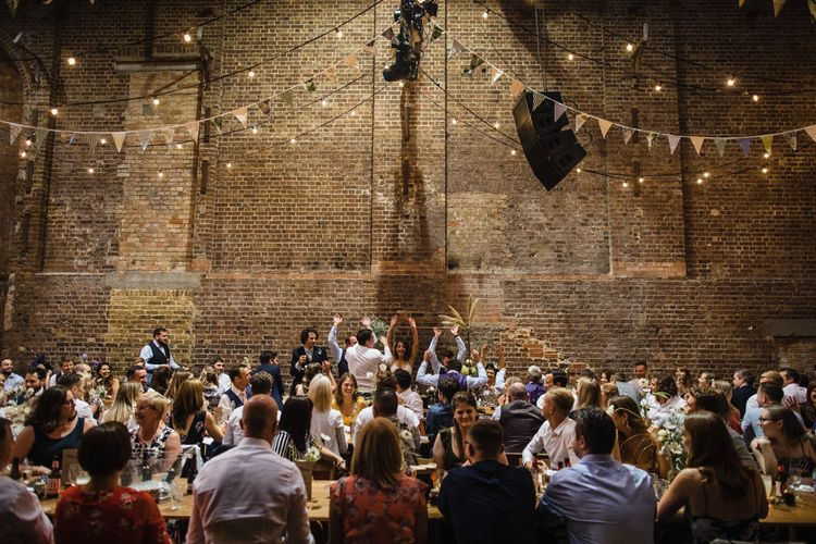 Wedding Reception at Village Underground | Festoon Lights | Multicoloured Bunting | Bride in Grace Loves Lace Gown with Spaghetti Straps and Oversized Rose Embroidery | Groom in Navy Three Piece Suit from Yardsmen | Shoreditch Wedding at Village Underground with Bride in Grace Loves Lace | Chris Barber Photography