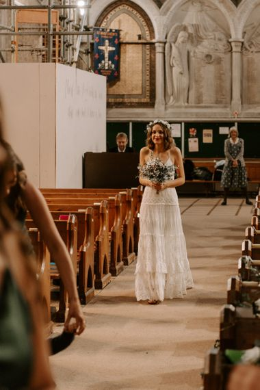 Bride walking down the aisle at intimate church ceremony wearing boho style Spell And The Gypsy dress
