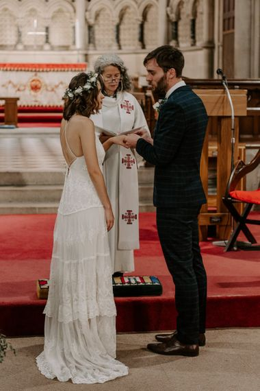 Bride and groom tie the knot at intimate church ceremony with bride wearing Spell And The Gypsy boho dress