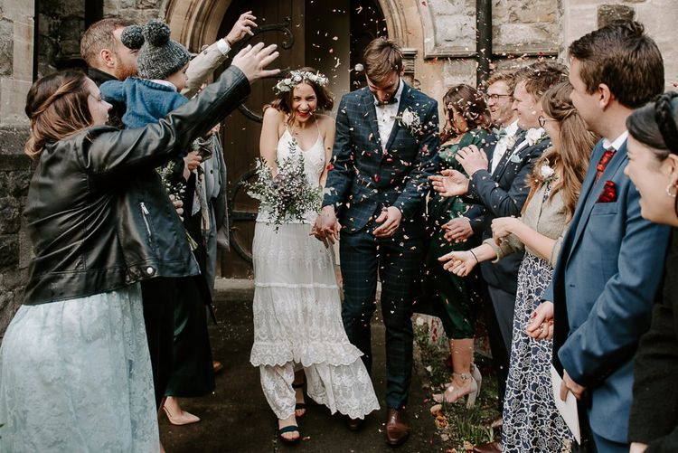 Church confetti shot with bride wearing Spell And The Gypsy boho dress teamed with a white floral crown and bouquet
