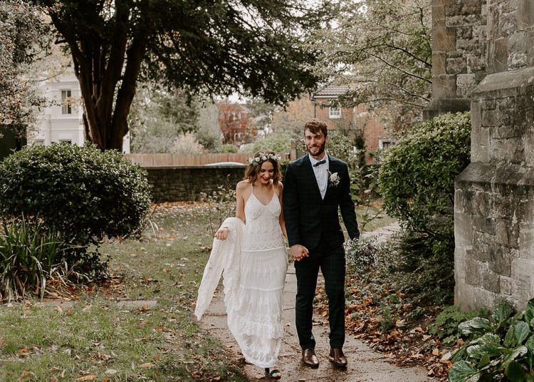 Bride wearing a Spell And The Gypsy boho dress with white floral crown and red lip plus groom in checked suit and bow tie