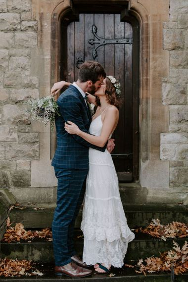 Bride and groom embrace wearing boho style dress with white floral bouquet and hair crown