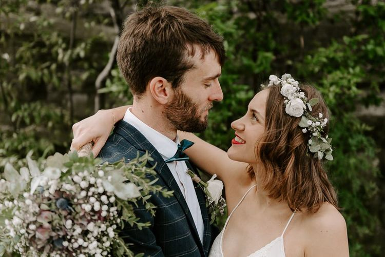 Bride wearing white floral hair crown with red lip and groom wearing checked suit with green bow tie