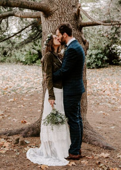 Bride and groom steal a moment with groom wearing checked suit and bride in a laced boho dress