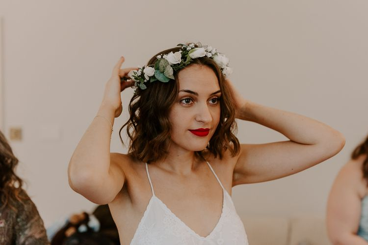 Bride wearing Spell And The Gypsy bridal dress with white floral flower crown and red lipstick
