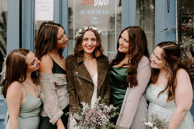 Intimate autumn wedding reception with boho bridal dress teamed with suede jacket and green bridesmaid dresses