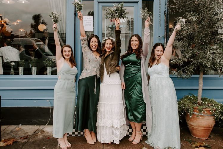 Bride wearing beautifully laced Spell And The Gypsy dress with bridesmaids wearing green dresses plus white floral bouquets