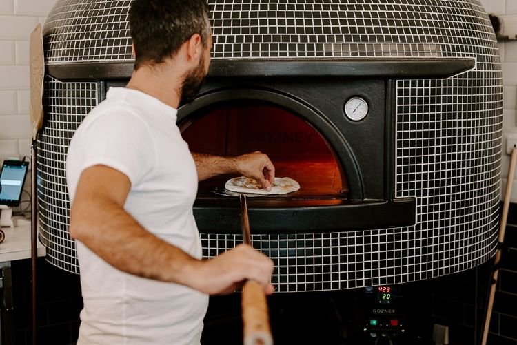 Pizza making at Italian restaurant for intimate reception in autumn
