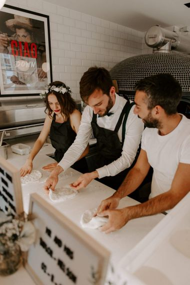 Bride wearing a white floral hair crown making pizzas with the groom at Italian restaurant wedding reception
