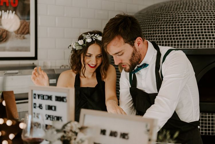 Bride and groom at Italian restaurant for intimate reception with pizza making and black and white wedding signs