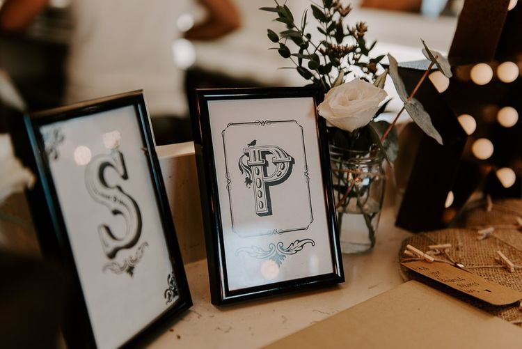 Black and white wedding stationery with white floral decor at intimate reception