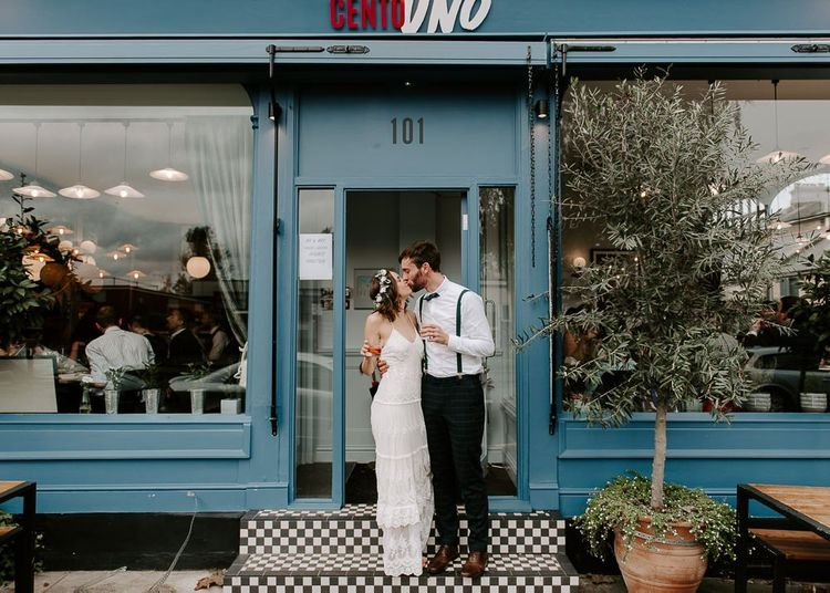 Bride and groom embrace outside of Italian restaurant for intimate reception wearing Spell And The Gypsy dress