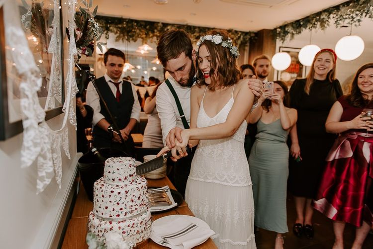 Bride wearing Spell And The Gypsy dress cutting the homemade dried flower cake with her groom