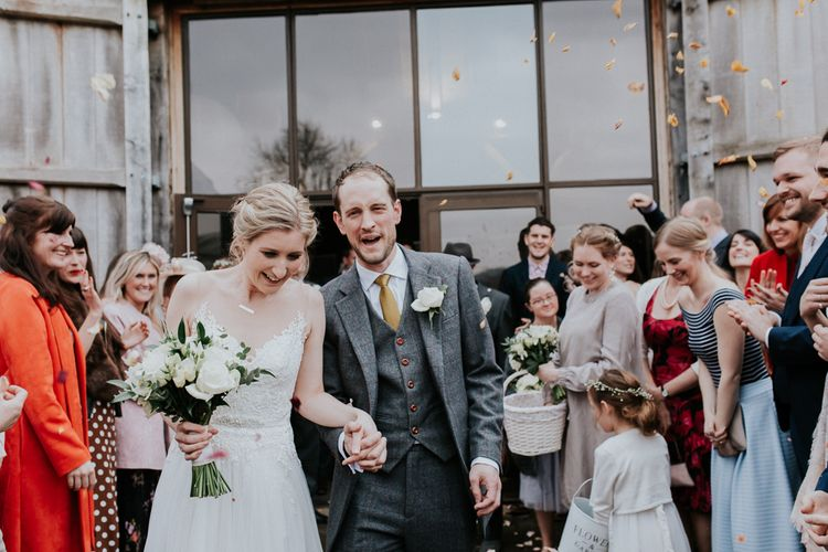 Confetti Moment   Bride in Essense of Australia Gown   Groom in  Grey Suit   Gold, Grey & Green Rustic Wedding at The Gilbert White's 16th Century Hampshire Barn   Joasis Photography